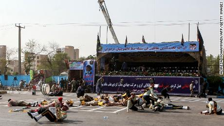 Injured soldiers lie on the ground after Saturday's attack on a military parade Ahvaz, Iran.